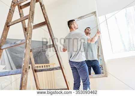 Young man hangs a mirror on the wall while moving into new apartment or new house
