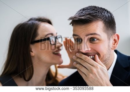 Portrait Of Happy Woman Whispering Secret Or Interesting Gossip To Handsome Man In His Ear