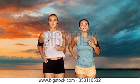 fitness, sport and healthy lifestyle concept - young women or female friends with earphones wearing armbands with smartphones and running over sea and sunset sky on background