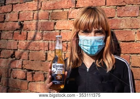 Girl With Medical Mask Holding Corona Beer. In The Middle Of Cornavirus (covid-19) Pandemic And Glob