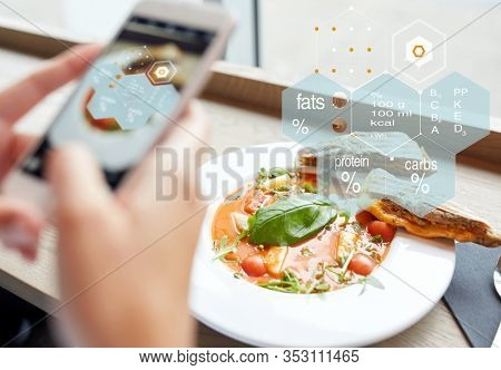 food, eating, technology, culinary and people concept - woman hands with gazpacho soup photo on smartphone screen and nutritional value chart at restaurant