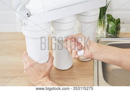 Plumber Or Man Hand Holding Installation Key And Replace A Water Filter Cartridges At Home Kitchen.