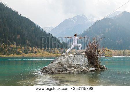 A Man Practices Yoga On A Background Of Mountains. Pose Virabhadrasana 2 Or Warrior