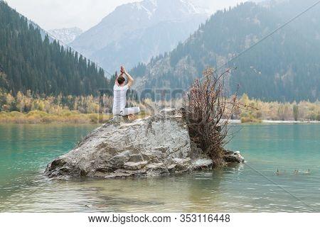 Young Zen Man In Meditation. Outdoor Yoga In Mountain Lake. Exercise Agni Stambhasana.