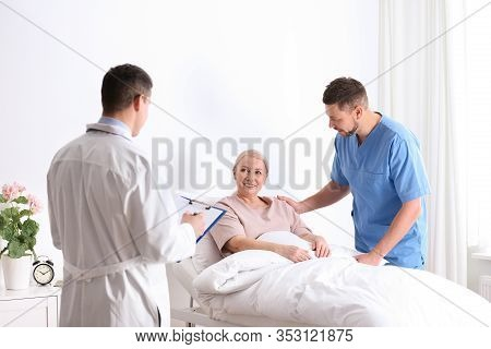 Doctor And Male Nurse Visiting Patient In Hospital Ward