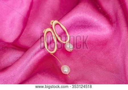 Modern Asymmetrical Golden Earrings With Pearl Beads On Pink Silk Background