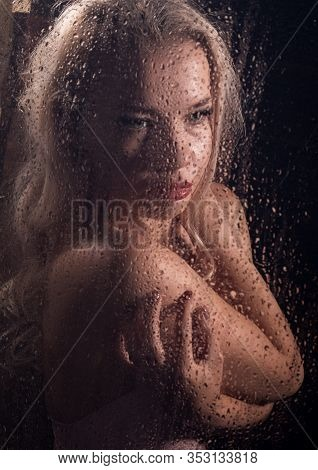 Beautyful Blonde Woman Behind Wet Glass On A Dark Background, Woman Takes A Shower
