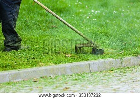 Man Mowing Green Grass Using Brushcutter Mower. Seasonal Garden Cleaning Moder Objects Concept.