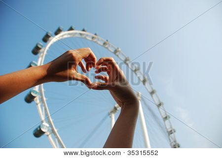 Human Hand Forming A Love Symbol With Furish Wheel Background