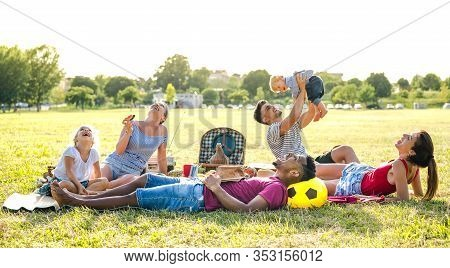 Young Multiracial Families Having Fun Playing With Kids At Pic Nic Garden Party - Multiethnic Joy An