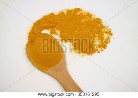 Turmeric Powder In A Wooden Spoon (curcumin) Isolated On A White Background Is An Ingredient In Turm
