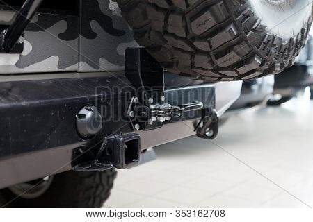 Close-up On A New Black Tow Hitch Installed On A Offroad Car With An Iron Black Bumper In A Vehicle