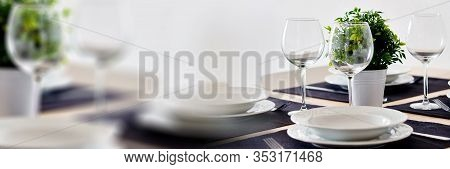 Close Up View Table Setting Served For Dinner On Violet Place Mats Empty Wine Glasses Plates Flatwar