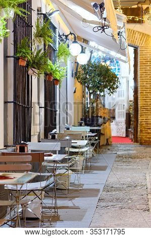 Charming Sidewalk Terraced Open Space Cafe, Empty Metallic Tables And Chairs In The Street Lit By La