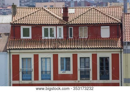 Several Colours Building With Several Windows, Roof And Sunlight.