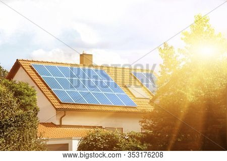 Solar Panels On The Tiled Roof Of The Building In The Sun.