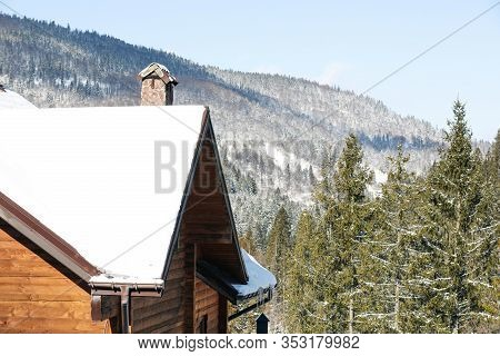Wooden Cottage Covered With Snow Near Conifer Forest