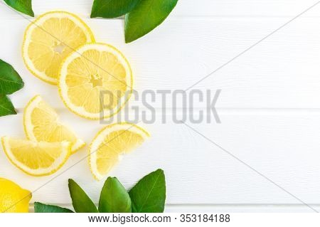 Fresh Sliced Lemon And Green Leaves On White Wooden Background. Flat Lay, Top View, Copy Space.