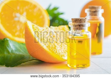 Natural Orange Essential Oil In Bottle And Cut Oranges Fruit On White Wooden Table.