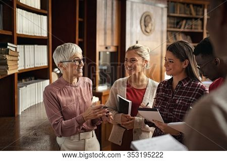 Happy university students talking with teacher in library. College professor with multiethnic class studying in library. Group of four focused clever students in conversation with senior teacher.
