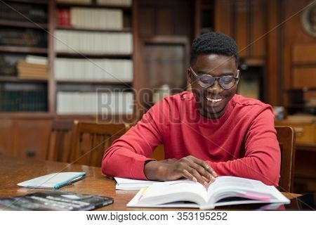 Happy young black student wearing spectacles reading text book. African american guy preparing for exams while sitting in high school library. Smiling college student sitting at desk and taking notes.