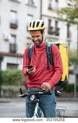 Food delivery man looking at smartphone on bike. Young delivery courier with bicycle controlling a customer address by phone with gps. Smiling rider wearing delivery backpack using smart phone.