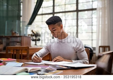 Male student researching with a book in a library. African american young man sitting at desk and taking notes in high school library. Focused serious student writing in a book and preparing an exam.