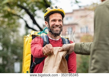 Delivery man giving package to customer. Smiling food delivery courier giving order while sitting on bicycle wearing company backpack and helmet. Happy driver giving lunch to client.