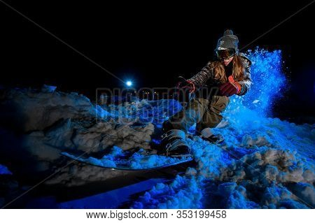 Female Freerider Slides On A Snowboard In Night