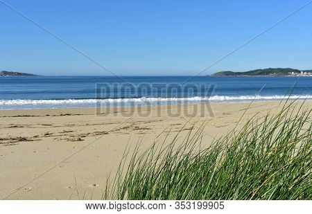 Beach With Grass On Sand Dunes, Blue Sky And Sea With Small Waves Breaking. Muxia, Coruña, Spain.