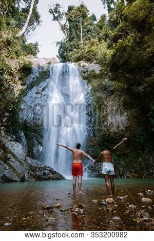 Couple Hiking To Waterfall In Thailand, A Tourist Is Enjoying The Beauty Of The Waterfall In Chumpho