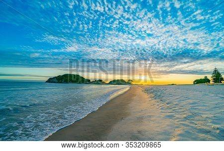 Mount Maunganui Main Beach With Moturiki Island As Sun Rises Over Horizon And White Puffy Clouds Wit
