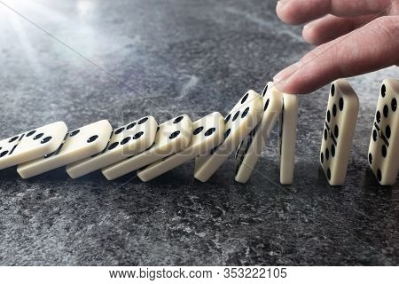 Close-up Of Male Hand Preventing Line Of Domino Tiles From Toppling And Falling, Prevention Of Domin