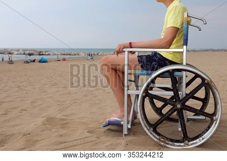 Disabled Boy In A Wheelchair Looks At The Sea From The Beach