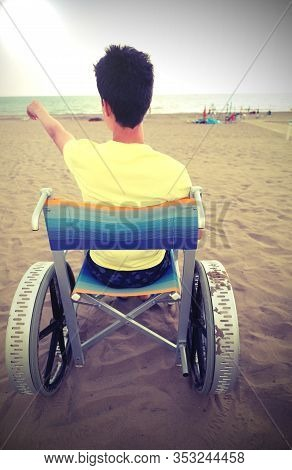 Young Boy On The Special Wheelchair With Big Wheels On The Beach With Old Toned Effect