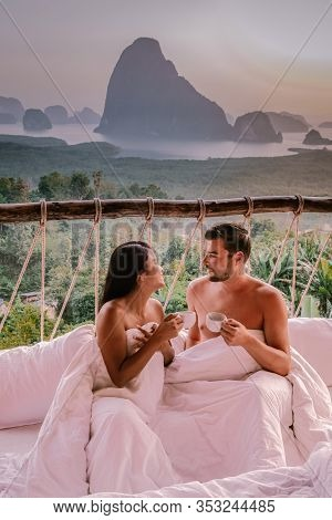 Couple Watching Sunrise In The Mountains Of Phangnga Bay During Sunrise, Couple Watching Sunrise At