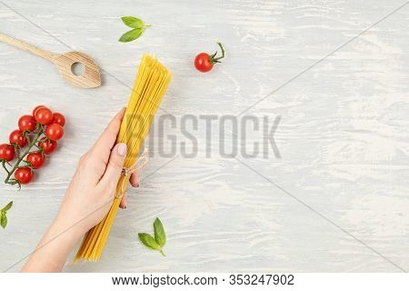 Flat Lay Of Woman Hand Holding Spaghetti And Ingredients For Cooking Italian Pasta. Spaghetti, Tomat