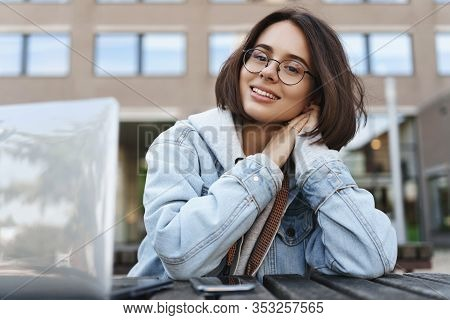 Smiling Dreamy Young Woman In Glasses Looking At Camera Happy, Relaxing Having Conversation With Cla