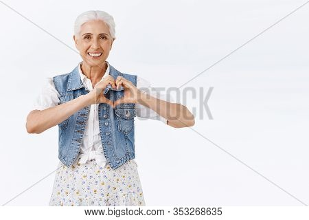 Charming Lively And Carefree Caucasian Senior Woman, Old Lady Showing Heart Sign Express Love Or Car
