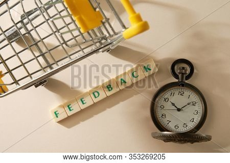 FEEDBACK word made with square blocks with shopping cart and pocket watch