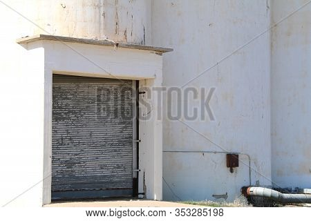 A White Grain Farm Silo Building Loading Receiving Door In The Afternoon