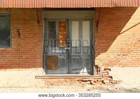 A Pair Of Locked Vintage Double Warehouse Shipping And Receiving Doors  With Afternoon Shadows