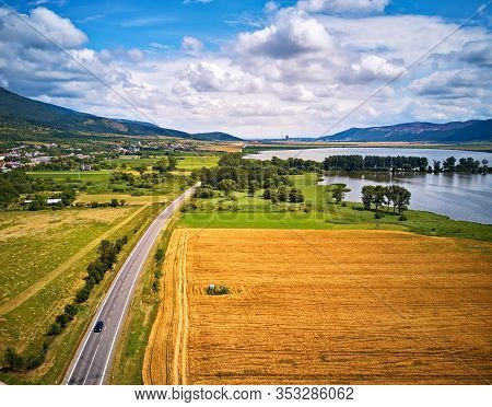 Summer Landscape With Fields, Meadows, Lake And Mountains. Road On The Lakeside