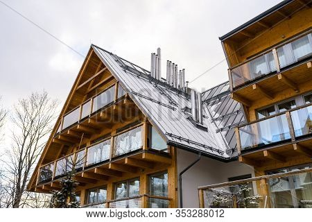 A Modern Wooden Villa With Lots Of Large Windows And Balconies With A Tin Roof Covered With Snow And