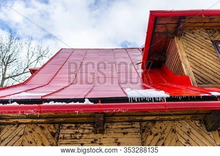 Wooden House In The Polish Mountains With A Red Tin Roof Covered With Snow And Ice.
