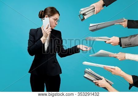A Business Young Woman In A Business Suit Speaks On The Phone, And At This Time Many Hands Hold Out