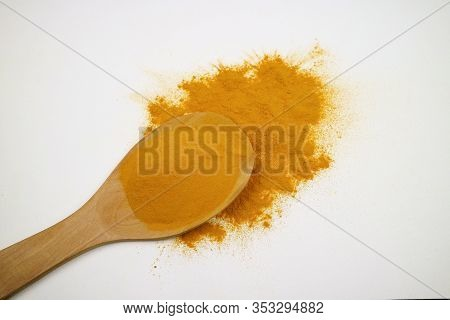 Turmeric Powder In A Wooden Spoon (curcumin), Isolated On A White Background, Is An Ingredient In Tu