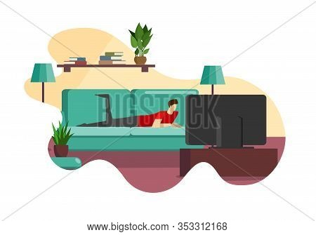 Young Lazy Man In Home Clothing Lying On Comfortable Couch In Front Of Television Screen In Living R