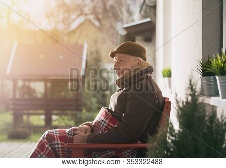 Senior Man Sitting On Bench Covered With Blanket On Porch And Enjoying Fresh Air On Cold Winter Day