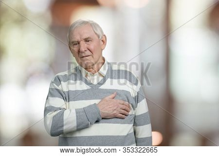 Old Man With Sudden Pain In The Heart. Abstarct Blurred Background.